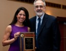PHHP Dean Michael G. Perri presents the Teacher of the Year award to Dr. Michelle Troche at the college's spring convocation ceremony.