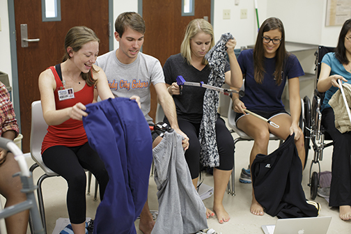 In the blended learning format, occupational therapy students have more time for hands-on learning. Here, students in the therapeutic skills class learn dressing skills, including the use of adaptive equipment, for patients who have experienced a stroke or hip fracture.