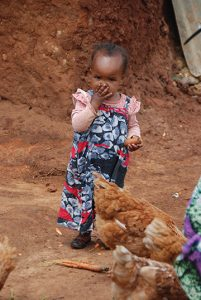young girl outdoors with chickens