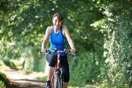 Woman Riding Bike Through Countryside