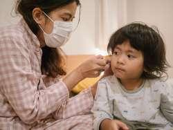 woman checking child's temperature