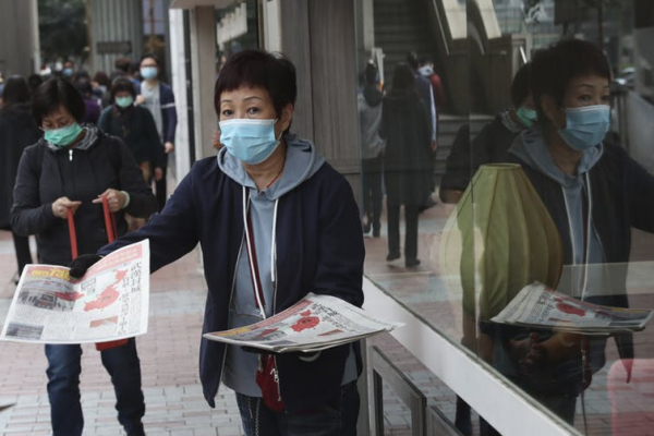 woman in mask passes out flyers