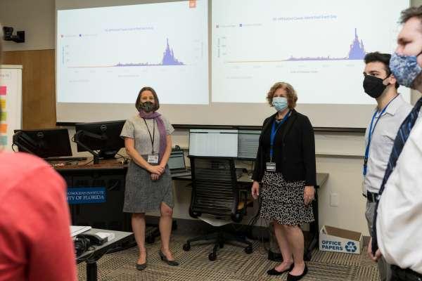 group of masked people in meeting room