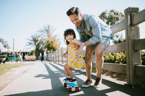 A dad helps his little girl go skateboarding