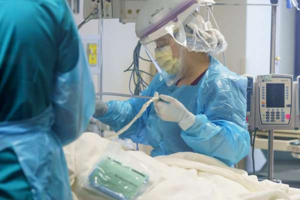 Becky Hunter, RN, tends to one of her COVID patients on ICU Unit 82 at UF Health in Gainesville, FL.