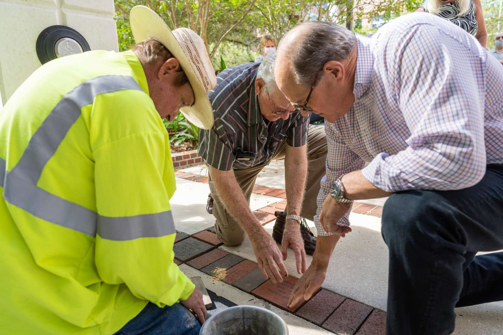 Robert Frank and Lou Stallings lay brick in front of building entrance
