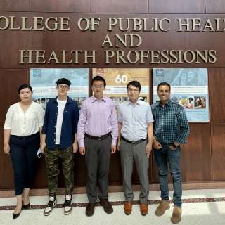 Zhoumeng Lin lab posed in front of PHHP history display.